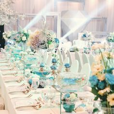 tiffany n co table setting arrangement. the combination of white and blue roses, baby blue hydrangea and white gerbera with touches of white and silver glittery accessories.