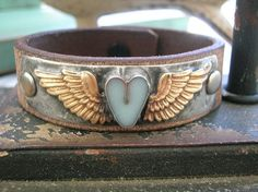 Winged heart leather cuff bracelet  Little Wing  by 3DivasStudio A petite hand-forged heart-shaped bezel is centered between angel wings. All soldered onto a brass backplate with lead-free, nickel-free solder and secured with rivets onto premium European distressed leather. Hand-rubbed with an aging patina to add to its rustic charm