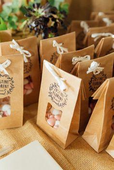 Bonbonnière mariage champêtre:  Dragées blanches et roses dans une pochette couleur brun naturel avec ficelle en papier et tampon personnalisé