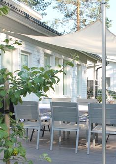 A white triangular canopy attached to aluminum posts with springs on each end in the backyard
