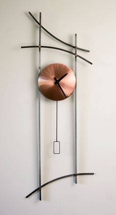 Asian Wall Clock by Ken Girardini and Julie Girardini. Long steel lines evoke the exotic strokes of Chinese calligraphy and provide cool contrast to the bright copper face and details. Signed and dated. Uses one AA battery (included).