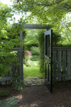 Here is a full-size door, inserted in a humble wooden fence. Its presence heightens the sense of entry into a verdant side garden. There's even a stone threshold over which to step.