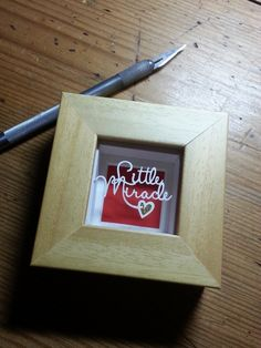 'Little Miracle' - Miniature Original Papercut This little papercut is cut from a single sheet of cream textured paper, with teeny weeny layered gold sparkly heart detailing. Magically floating over a red background casting pretty shadows.