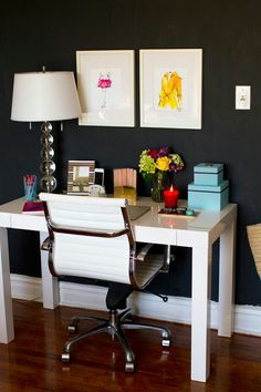 Beautiful clean home office space. The white table, chair and lamp contrast beautifully against the navy wall.
