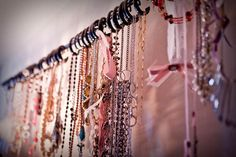 DIY necklace organizer using a curtain rod and shower curtain hooks.