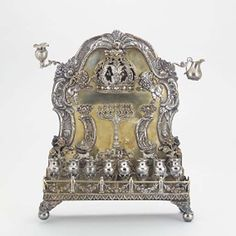 A POLISH SILVER-GILT HANUKKAH LAMP  MARK OF ANTONI RIEDEL, WARSAW, 1887  The cartouche shaped back plate decorated with a central menorah motif, centred within columns, further decorated with lions and an openwork crown, all within a foliate scroll and rocaille border, the shaped rectangular base suppored on scroll and ball feet and with eight fonts, each supported on an eagle, with a servant light and a vessel for oil - 13 7/8in. (35.2cm.) high, 42oz.