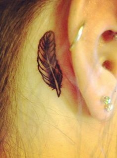 Feather tattoos for girls come in all shapes and sizes, but one of the most popular is the small feather tattoo inked behind the ear. This girl's feather tat is super small and is inked in black and white behind her right ear. The feather tattoo meaning is obviously something personal or ...