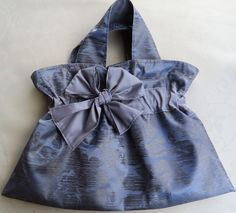 """This beautiful handmade plush grey BOWTASTIC BAG is very strong and resilient and looks amazing. It is great for an evening out, dinner parties, work or just to tote around town. This bag is fully lined in grey and has an inner pocket for keys, mobile phone, glasses and purse. Keep your things secure with a snap magnetic clasp. The contrasting design gives this bag a gorgeous gathered feature enhanced by a satin bow. This bag measures 18"""" wide x 13"""" tall. The handles are 3"""" x 18""""."""
