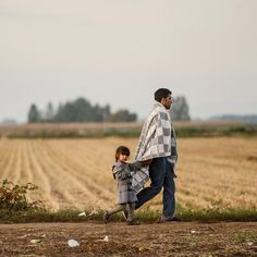 September 21, 2015: A man and his child walk the last few kilometres from Serbia to Croatia as more migrants continue to arrive by bus. Visit amnesty.org and join 1000s of you signing our petition to make #RefugeesWelcome!