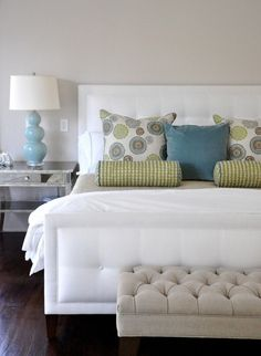 White upholstered bed with green and blue accents
