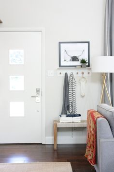 "We don't have a true entryway or foyer. The front door opens up into the living room. The small area behind the chair acts as our ""entry."" Peg hooks give guests a place to hang their coats and the bench is a great spot for stashing deliveries until we open them."