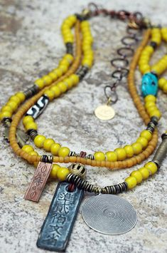 African Inspired Tribal Yellow Glass and Mixed Media Pendant Necklace ~ Kianga      Old Yellow Glass Trade Bead, African Brass, Bone, Turquoise, Copper Fetish, Silver Spiral and Chinese Coin Multi-Media Pendant Necklace $275.00