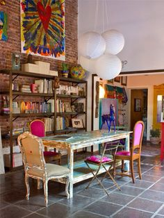 Amazing creative living space... Colour, wood and books, I want exposed brick so badly!
