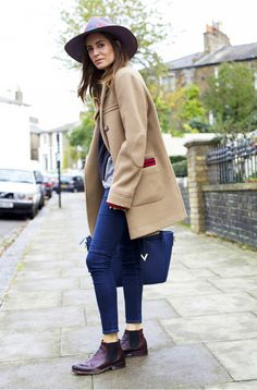 Gala Gonzalez wears layered tops, a camel coat, skinny jeans, a navy tote bag, fedora, and chelsea boots