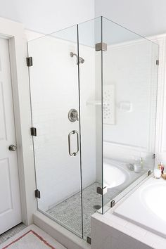 frameless glass shower next to tiled tub. like the border around the edge of the subway tile