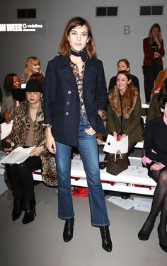 Alexa Chung wears a floral button-down blouse, neck scarf, navy blue peacoat, blue jeans, and black boots