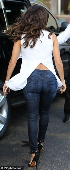 Scintillating: Eva wore a ruffled white top along with skinny dark blue jeans and strappy ...