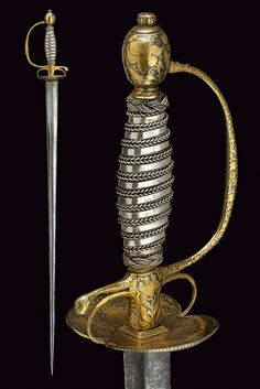 18th Century Straight blade of triangular section, with wider base; one-quillon iron hilt entirely decorated with beautiful, floral motifs in gold on dark ground; wooden grip with silver binding and moor's heads.