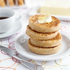 Four stacked crumpets on a plate topped with butter