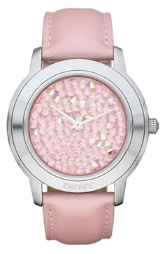 DKNY 'Large Round Rocky' Metallic Strap Watch in Pink.  Glamour exudes from a jumble of faceted jewels paving a three-hand watch face. A logo-etched case and shimmering leather strap add a polished finish.