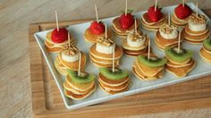 mini pancake stacks with assorted fruit piece topping. serve with maple syrup.