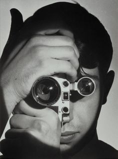 "Born in Paris, Photographer Andreas Feininger studied architecture in Germany, using a camera as an aid in creating his building designs. He emigrated to the U.S. in 1939, and in 1943 became a staff photographer for Life magazine where he completed more than 430 assignments in 20 years. Here, Feininger uses a camera to build a creative portrait of fellow photographer Dennis Stock. "" The Photojournalist (Dennis Stock, Magnum photographer)"", 1951 Gelatin silver print."