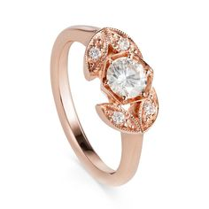 Shop this beautiful piece designed by Yasmn Everley. The central diamond of this engagement ring is a 0.43ct old European cut taken from an antique brooch and set into a distinctive hexagon. The four leaf-like shapes each contain a tiny diamond and have a millgrain edging as a nod to vintage design. #rosegold #engagement #weddingring #vintagejewellery