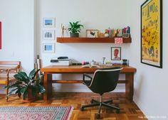 Espaço de trabalho com móveis de madeira, plantas, tapete étnico e muitos quadros.