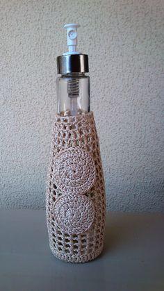 Crochet - Le he dado un nuevo aire a esta botella de cristal con colonia fresca. La he vestido con ganchillo de color beig, queda muy bien con la decoración del baño.