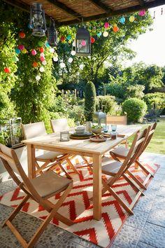 Pour aménager une terrasse, rien de compliqué. On choisit un tapis d'extérieur pour apporter de la couleur, du mobilier à l'aspect bois pour le côté naturel. Côté lumière, on mixe les guirlande et les lampions, pour le style et les longues soirées d'été. #castorama #inspiration #decoration #ideedeco #tendancedeco #jardin #exterieur #amenagement #terrasse #mobilierdejardin #table #chaise #guirlandelumineuse