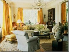 Living room inspiration. big yellow curtains. Gold and crystal touches. middle eastern influence in sculpture and pottery.