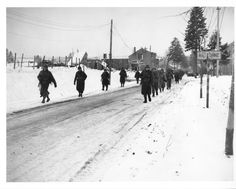 Members of the 101st Airborne Division move out of Bastogne, Belgium, to drive the Germans who have besieged them for ten days, out of a neighboring town. This photo was taken while Bastogne was still under siege. 12/29/44.