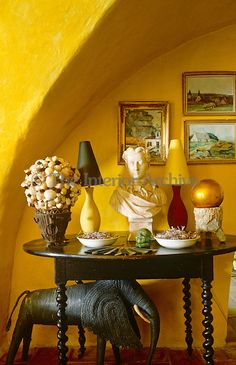 In an alcove of the salon a white marble bust placed on an antique table creates a pleasing contrast to the bright yellow walls ~ Provence