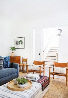 Boho-chic living space with matching leather armchairs, and a denim sofa