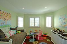 Storage with a white picket fence motif echoes the fence that greets visitors as they enter this Brentwood home. The light green walls, polka dot rug and vibrant blue and pink chairs keep this girl's bedroom feeling energetic. A confetti comforter continues the colorful, fun feel while anchoring the room with its dark color.