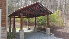 Timber carport design with stacked stone column wraps installed around the base of each supporting post.