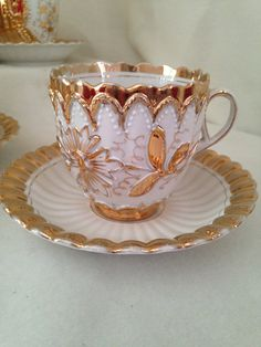 Pretty Gold Embossed Floral Tea Cup and Saucer Set. Seems to be Gold sprayed, heavy to lighter at edges. Shaded affect, really unique and beautiful. Ruffled edges and ribbed on both the cup and saucer. Japan China dates to around WW11 era. Good condition, 1 very tiny chip on bottom of saucer and hairline on handle bottom.