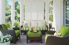 Private Porch - 80 Breezy Porches and Patios - Southernliving. Louvered shutters add a little privacy to this porch space and fresh apple green accents punch up the color scheme. The creaminess of the white columns and louvered shutters create a beautiful base for the fun—slightly cheeky—brightness of the apple green upholstered cushions. The mix of cream and apple green mirrors the contrast between the cream paint and verdant greenery beyond the patio. This porch's furniture is constructed…