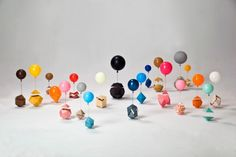 Little balloons lifting the lids off paper polyhedra. Magical work by Amy Watson.