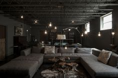 moody lounge, exposed bulbs, gray tweed sectional, moody vibes, natural tree stump coffee table, cityhomeCOLLECTIVE lounge