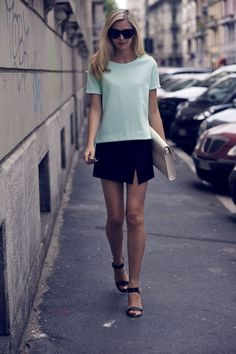 Jessica Stein is wearing a black asymmetrical mini skirt and clutch from Zara, pastel green top from top, sunglasses from Dolce & Gabbana an...