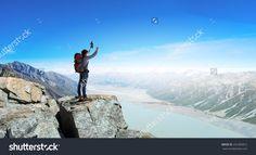 Mountaineer at peak of mountain enjoying natural landscape