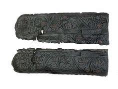 Leather knife sheath, now flattened open and in two pieces.Decorated on both front and back with incised foliate motifs and narrow panels of chevrons. The foliage is enhanced with impressed dots, possibly a scrolling vine. There are traces of red paint on the decorated surfaces. There is a side seam with edge/grain stitch holes. There are four suspension slots towards the opposite side to the seam. The sheath has a rather blunt, rounded end. Late 14th-15th century | Museum of London
