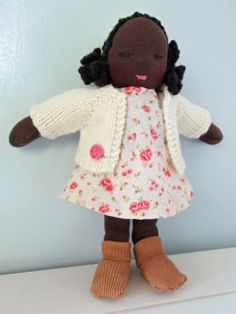 A little Waldorf inspired doll, with a rose strewn outfit and disposition.  Rosie is eight inches high and three inches wide at her waist, she is made from dark brown stockinette material, she has homespun hand crocheted hair that has been sewn on, her clothes are hand sewn and includes felt underpants, a simple rose strewn dress, a hand knitted cardigan,  and little brown socks. She is stuffed with wool.  Rosie is made up of small parts so if she is intended for a child, older than three…