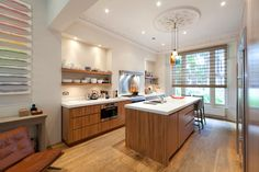 Terrific kitchen - color, open floating shelves, recessed lighting and bar with vegetable sink