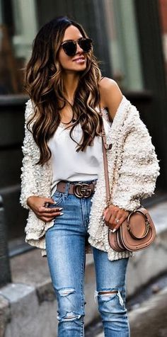 #winter #outfits white wool cardigan with crossbody bag, sunglasses, white spaghetti strap shirt and distressed blue-washed jeans