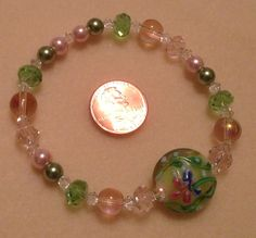 Stretch bracelet with glass beads and glass pearls in Spring colors, clear Swarvoski crystal spacer beads, and floral lampwork accent bead $20