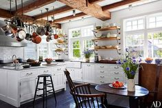 The kitchen's pot rack is from Ann-Morris, the reclaimed-oak open shelves feature brackets by Rocky Mountain Hardware, and the backsplash tile and farmhouse sink are by Waterworks; a Ralph Lauren Paint white was used on the Rivkin/Weisman–designed cabinetry, and the antique granite flooring is from Exquisite Surfaces.