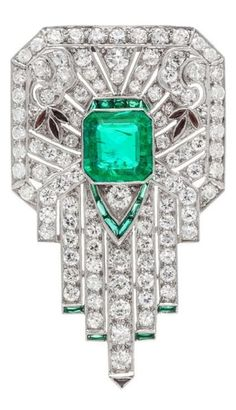 An Art Deco Platinum, Emerald, Diamond, and Multigem Clip Brooch. Of geometric openwork design with millegraine edgework, containing one octagonal step cut emerald measuring approximately 9.50 x 9.00 x 4.55 mm, numerous transitional brilliant and old European cut diamonds weighing approximately 3.55 carats total, seven calibré cut onyx, and 15 calibre cut simulated emeralds. #ArtDeco #brooch