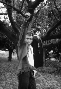 PUBLICITY PHOTO - GIANT or THE LEFT HANDED GUN?  - James Dean suggesting 'The Cowboy Look' - note fringed leather jacket and Levi's, as well as leather chaps hanging on tree limb in background.